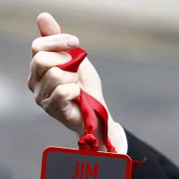A badge is held up before a Requiem Mass for the broadcaster Jimmy Savile in Leeds, England, in November 2011. A British children's charity says at least 500 people have reported abuse by the late entertainer, with the youngest alleged victim just 2 years old. | AP