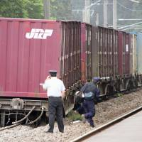 Railway maintenance workers check the site where two cars of a freighter train derailed on a section of the JR Esashi Line at Kikonai, southern Hokkaido, on Sunday morning. | KYODO