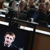 Former U.S. National Security Agency contractor Edward Snowden speaks to European officials via a video link during a parliamentary hearing on improving the protection of whistle-blowers, at the Council of Europe in Strasbourg, France, on Tuesday. The NSA released its first 'transparency report' Friday, as part of an effort to quell the firestorm over information released by Snowden. | AFP-JIJI