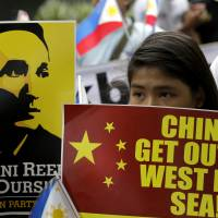 Protesters display placards outside the Chinese Consulate in the financial district of Makati, east of Manila, on Thursday, during a rally against recent reclamation and construction in the disputed Spratlys Islands group in the South China Sea. | AP