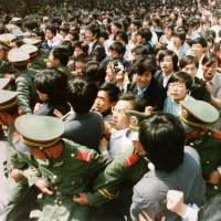 Jubilant students surge through a police cordon before pouring into Tiananmen Square during a pro-democracy demonstration on June 4, 1989. | REUTERS