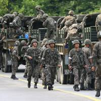 South Korean Army soldiers exit military trucks during an operation to find a soldier suspected of killing five comrades at an outpost near the tense border with North Korea in Goseong on Monday. | AP