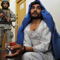 Afghan security personnel present an alleged Taliban fighter to the media at the Afghan National Army headquarters near Jalalabad in March. . | AFP-JIJI