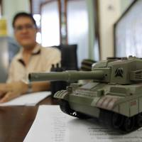 A toy tank is seen on the desk of an official as he works at Government House, after it reopened following a military coup in Bangkok on Monday.   REUTERS