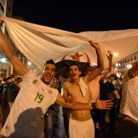 Thrilled: Algerian soccer fans celebrate on Thursday after the the national team advanced to the World Cup round of 16 for the first time. On the same day, Algeria and Russia settled for a 1-1 draw in their final match in Group H.     AP