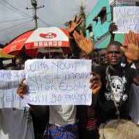 People protest outside a hospital as Liberia President Ellen Johnson Sirleaf visits the area after Ebola deaths in Monrovia on June 17. Seven people believed to have the Ebola virus have died in recent days in the first deaths reported in the Liberian capital since the outbreak began, a health official said Tuesday. | AP