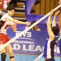 Rising above: Japan's Akihiro Yamauchi hits the ball against Argentina's frontline on Sunday. FIVB