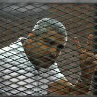 Canadian-Egyptian journalist Mohamed Fahmy gestures from the defendant's cage during a sentencing hearing in a courtroom in Cairo, on Monday. An Egyptian court on Monday convicted three journalists from Al-Jazeera English and sentenced them to seven years in prison each on terrorism-related charges, bringing widespread criticism that the verdict was a blow to freedom of expression. | EL SHOROUK NEWSPAPER/AP