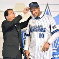 Perfect fit: Yulieski Gourriel is helped in to his uniform and hat by BayStars GM Shigeru Takada during a news conference on Monday. | KYODO