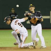 How about two: The Hawks' Yuichi Honda attempts to turn a double play as the Giants' Yoshiyuki Kamei slides into second on Saturday at Tokyo Dome. Softbank won 3-1. | KYODO