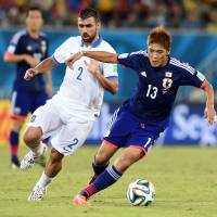 Nowhere to run: Japan forward Yoshito Okubo and Greece midfielder Giannis Maniatis (2) vie for the ball during their Group C football match at the World Cup on Thursday. | AFP-JIJI