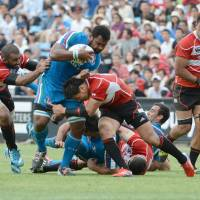 Kick it up a notch: Japan full-back Ayumu Goromaru leads the charges as a group of players converge on Italy's Manoa Vosawai (second left) during their match on Saturday. | AFP-JIJI