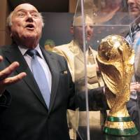 FIFA President Sepp Blatter gestures next to the World Cup trophy after a media conference in Sao Paulo on Thursday. The 2014 World Cup will be held in 12 cities in Brazil from June 12 to July 13. | REUTERS