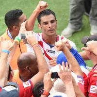 Ride the wave: Costa Rica defender Michael Umana celebrates with Costa Rican fans after a 1-0 win over Italy at the World Cup on Friday.   AFP-JIJI