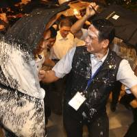 Security personnel protect Zhang Zhijun (center, white shirt), director of China's Taiwan Affairs Office, with bullet-proof suitcases in Taiwan as anti-China protesters attempt to douse him with white paint in Kaohsiung on Friday. | REUTERS