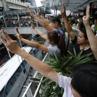 Protesters against military rule gesture by holding up their three middle fingers in the air, during a brief demonstration at a shopping mall in Bangkok on Sunday. Thailand's military government sent thousands of troops and police into central Bangkok on Sunday to stop any demonstrations against its seizure of power, and some shopping malls and train stations closed to avoid trouble. According to some, the three-fingered gesture stood for freedom, equality and brotherhood.   REUTERS