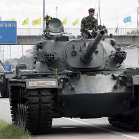 This file photo from September 2006 shows a column of military tanks guarding a highway in suburban Bangkok as the military tightened its grip on power two days after a bloodless coup. The last time Thailand had a coup, in 2006, the stock market crashed when the kingdom imposed draconian capital controls. This time around, investors hope the generals have learned their lesson. | AFP-JIJI