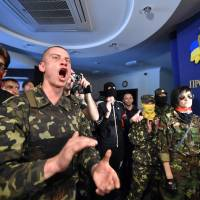 'Maidan' self-defense activists and activists of the Ukrainian ultra-nationalist Right Sector party shout slogans as they storm the Kiev City Prosecutors' office on Friday. The protesters stormed the building demanding the city prosecutors' resignation and a purge of prosecutors who took part in the repressions of the anti-government protests on Kiev's Independence Square. | AFP-JIJI