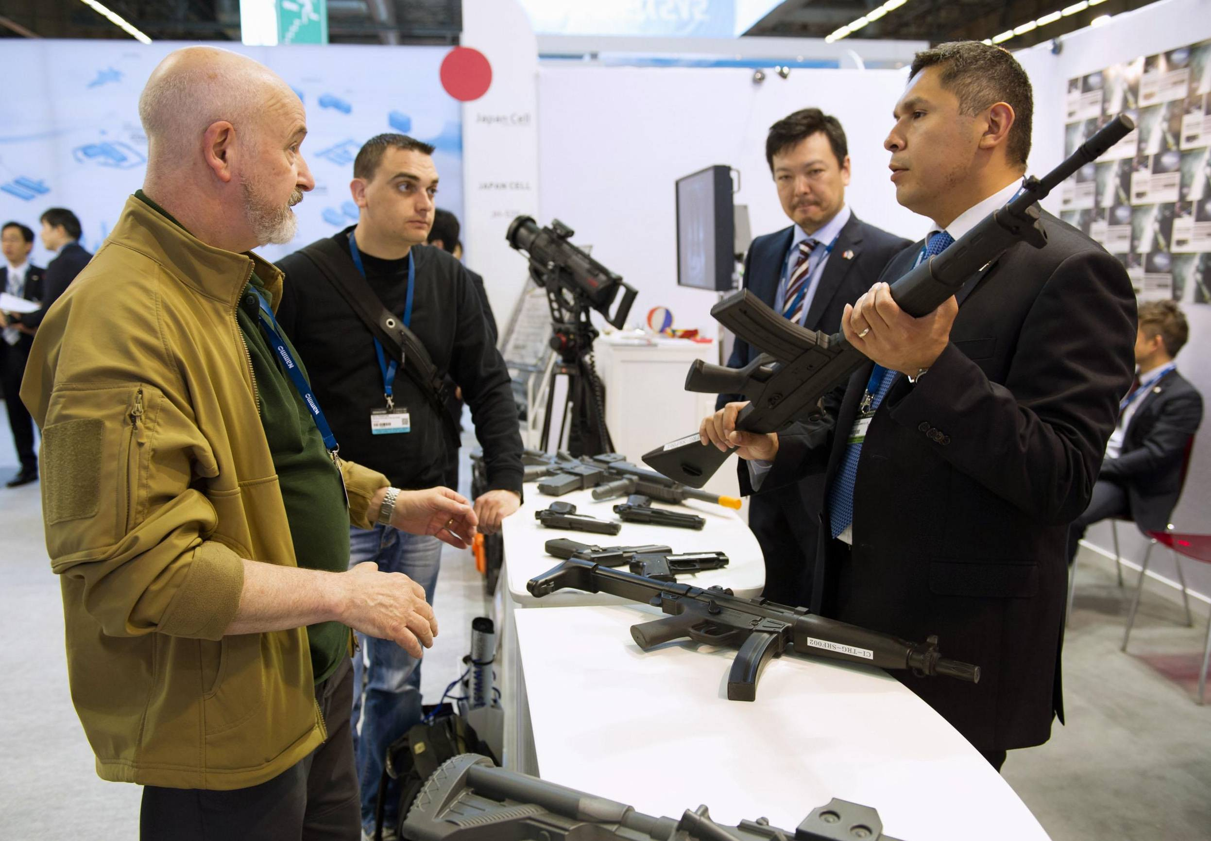 People check out rubber machine guns made for training purposes at the Japan pavilion of the Eurosatory defense fair on Monday in Paris. This is the first international weapons show to see exhibitions by Japanese companies. | KYODO