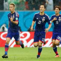 Keisuke Honda (left) celebrates his goal Saturday with his teammates Maya Yoshida (center) and Yuya Osako during the first half of their Group C soccer match in Recife, Brazil. | REUTERS