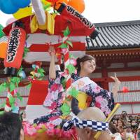 Osaka's first summer festival of the year: An Aizen Festival contestant entertains the crowds as she is paraded through the streets on a palanquin.