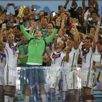 Germany goalkeeper Manuel Neuer lifts the World Cup trophy with his teammates after defeating Argentina 1-0 in Sunday's final at the Maracana stadium in Rio de Janeiro. | REUTERS