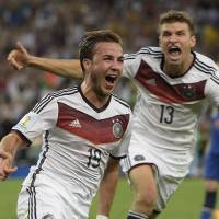 Germany midfielder Mario Goetze (left) celebrates with teammate Thomas Mueller after scoring in the 113th minute of Sunday's final against Argentina.