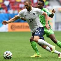 Nigeria midfielder Ogenyi Onazi (right) view for the ball with France forward Karim Benzema during Monday's round of 16 match at the Mane Garrincha National Stadium in Brasilia. | AFP-JIJI