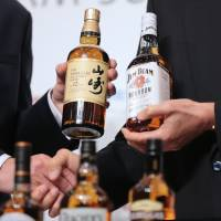Nobutada Saji (right), chairman and chief executive officer of Suntory Holdings Ltd., shakes hands with Matt Shattock, chief executive officer of Beam Suntory Inc., while holding bottles of spirits made by the companies, during a photo session in Tokyo on May 15. | BLOOMBERG