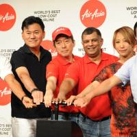 AirAsia Group CEO Tony Fernandes (third from right) and guests, including Rakuten Inc. chief Hiroshi Mikitani, announce on Tuesday the return of the low-cost airline to Japan after its bitter split with All Nippon Airways. | AFP-JIJI