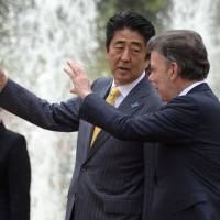 Prime Minister Shinzo Abe chats with Colombian President Juan Manuel Santos during a welcoming ceremony at Narino Palace in Bogota on Tuesday.   AFP-JIJI