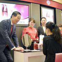 Shiseido Co. President Masahiko Uotani (left) speaks to a customer at Hankyu Department Store's Umeda outlet in the city of Osaka on Wednesday as the major cosmetics company released a new skin product strategically developed for the international market. | KYODO