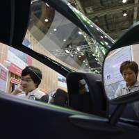 Visitors look at a Toyota i-ROAD electric personal mobility vehicle at the ITS World Congress in Tokyo last October. | BLOOMBERG