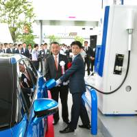 Chihiro Tobe, director of the Hydrogen and Fuel Cell Promotion Office at the Natural Resources and Energy Agency, charges a fuel-cell car as Iwatani Corp. President Masao Nomura watches at a new hydrogen filling station in Amagasaki, Hyogo Prefecture, on Monday. | KYODO