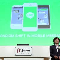 Akira Morikawa, chief executive officer of Line Corp., makes a speech at IT Japan 2014, hosted by Nikkei Business Publications Inc., in Tokyo on July 4. | BLOOMBERG