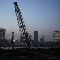 Heavy machinery is silhouetted against the skyline on a construction site at dusk in the Toyosu area of Tokyo, on May 13. | BLOOMBERG