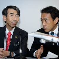 President and CEO of Mitsubishi Aircraft Corporation Teruaki Kawai (left) and Vice President of Corporate Planning and Business Strategy Hank Iwasa speak during a press conference at the Farnborough air show in Farnborough, England, on Monday.  The biennial event sees leading companies from the aviation industry showcase their latest technology. | AFP-JIJI