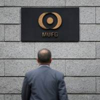 A man walks toward signs for Mitsubishi UFJ Financial Group Inc. outside its headquarters in Tokyo in May.   BLOOMBERG