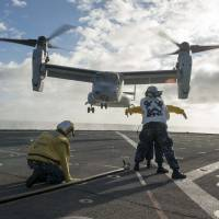 U.S. Navy sailors on July 8 aboard the amphibious dock landing ship USS Rushmore direct an MV-22 Osprey onto the flight deck for a personnel transfer during the at-sea phase of exercise Rim of the Pacific (RIMPAC) 2014. Japan and Israel are believed to be the first nations to purchase the aircraft. | AFP-JIJI