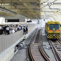 Members of the press and the public are led onto the third-floor train platform of Keikyu Kamata Station in September 2012 for a preview of the renovated facility before it opened the following month. | KYODO