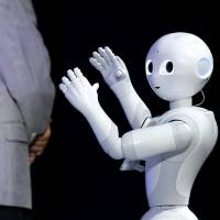 The humanoid robot Pepper, developed by SoftBank Corp.'s Aldebaran Robotics unit, performs next to Masayoshi Son, chairman and chief executive officer of the telecom giant, at SoftBank World 2014 in Tokyo on Tuesday. | BLOOMBERG