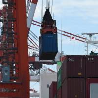 A container is loaded onto a cargo ship at a Tokyo pier on Tuesday. Japan recorded a current account surplus for the fourth straight month in May. | AFP