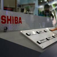 An attendee pushes a button on a model of the AP1000 reactor at the Toshiba Corp. booth at the the 22nd World Energy Congress in Daegu, South Korea, in 2013. | BLOOMBERG
