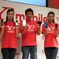 Flanked by models, Ymobile Corp. President Eric Gan shows off the fledgling company's first smartphones at a news conference in Tokyo on Thursday. | KAZUAKI NAGATA