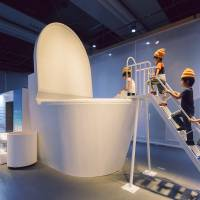 Kids get ready to be flushed down a giant toilet to experience a virtual sewage system