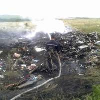 A man works at putting out a fire Thursday at the site of a Malaysia Airlines Boeing 777 plane crash in the settlement of Grabovo in the Donetsk region. | REUTERS