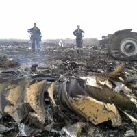 Emergencies Ministry members work at the site of a Malaysia Airlines Boeing 777 plane crash in the settlement of Grabovo in the Donetsk region of Ukraine on Thursday. The airliner was allegedly shot down by pro-Russian militants, killing all 295 people aboard. | REUTERS