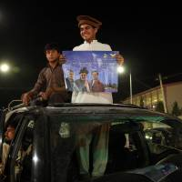 A supporter of Afghan presidential candidate Ashraf Ghani Ahmadzai holds up his poster as he and scores of others celebrate in Kabul on Monday. | AP