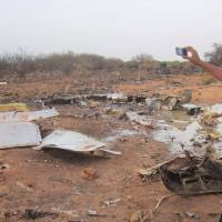 A man takes a picture of the crash site of Air Algerie Flight AH5017 near the northern Mali town of Gossi on Thursday. Poor weather was the most likely cause of the crash, which killed all 118 people on board the jetliner. | REUTERS