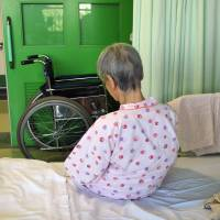 An Alzheimer's patient sits on her bed at a Tokyo hospital in August 2009.   BLOOMBERG